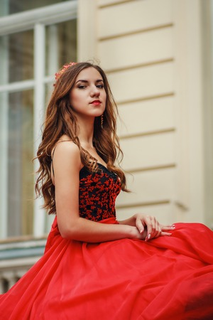coronet: Beautiful young woman in red dress with corset and coronet