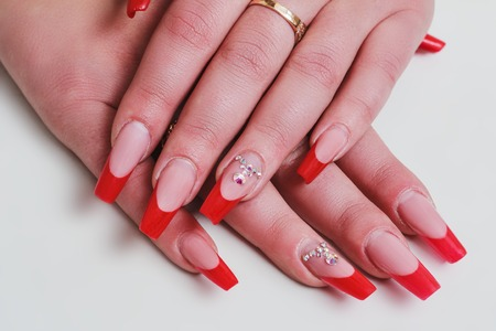 Red French Nail Art With Rhinestones On White Background Stock Photo