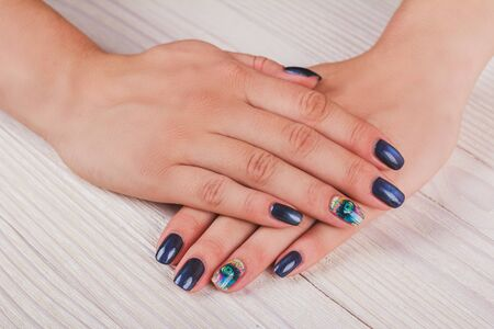 naildesign: Dark blue nail art with print eye on light wood background