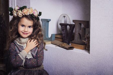 coronet: Small beautiful girl dressed in retro style with flower coronet Stock Photo