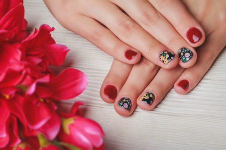 acrylic nails: Red nail art with printed flowers on light wooden background Stock Photo
