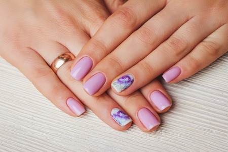 Lilac nail art with printed flowers on light wooden background