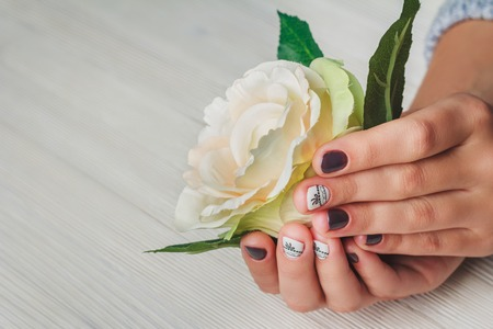 finger bow: Violet nail art with printed white bow on light background Stock Photo
