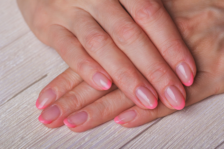 french ethnicity: French nail art in light pink colour on light wooden background Stock Photo