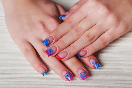 french ethnicity: French nail art in blue and red colors on wooden background
