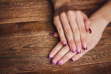french ethnicity: French nail art in purple color on wooden background Stock Photo