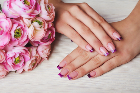 French nail art in purple color on wooden background Stock Photo