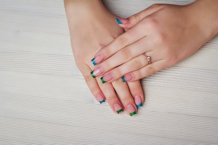 french ethnicity: French nail art in blue and green color on wooden background