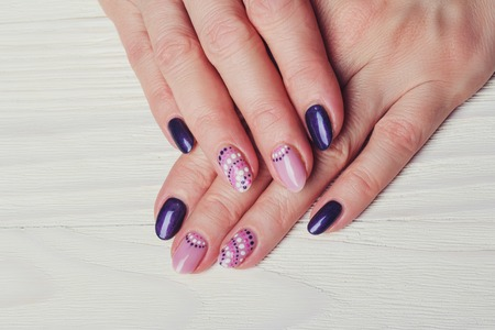 finger nail: Nail art with purple and pink colors on wooden background