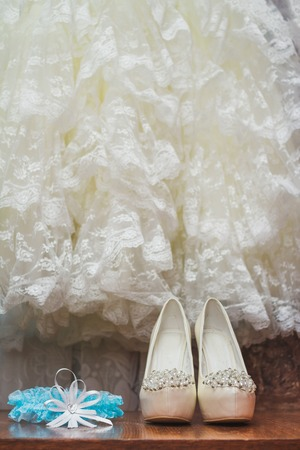 garter: Wedding shoes and blue garter on the dress background