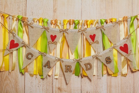 string together: Cards Wedding letters hanging sign with ribbons on light wooden background Stock Photo
