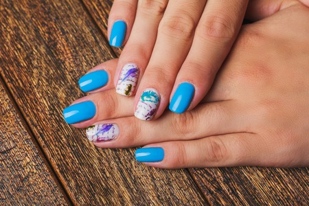 naildesign: Light blue nail art with feathers print on wooden background Stock Photo
