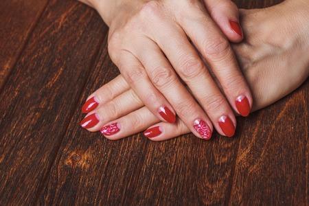Festive red nail art on dark wooden background