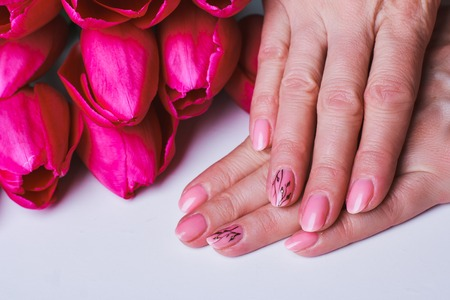 Pink nail art with flowers on white background Stock Photo