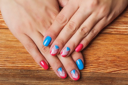 Nail art with bright pink and blue chevron pattern on wooden background Stock Photo