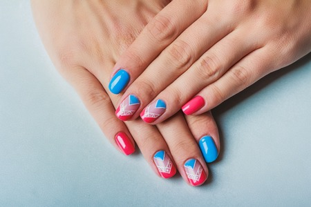 Nail art with bright pink and blue chevron pattern on light background Stock Photo