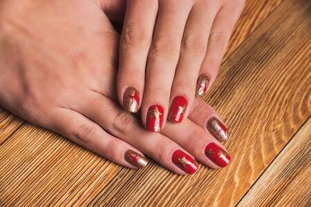 Festive nail art with stars in red and gold colors