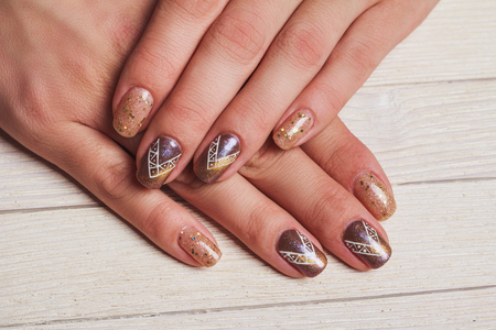 Gold nail art with tinsels on wooden background