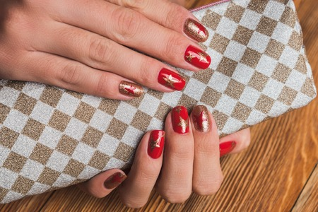 Festive Nail Art With Stars In Red And Gold Colors Stock Photo