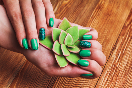 Turquoise Nail Art With Tinsels On Wooden Background Stock Photo