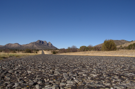 vast: Very low angle view of a road in the region of the Davis Mountain in the desert of western Texas