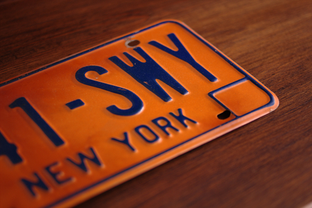 motor vehicle: Side view of a retro or vintage syle New York State motor vehicle licence plate above a wooden structure Stock Photo