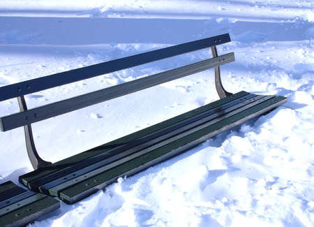 wintery day: Bench almost covered in snow in a park
