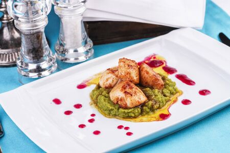 Pan-seared scallops with pea puree with cranberry sauce