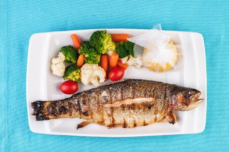 Mediterranean dish, European cuisine. whole fish baked in the oven, served with steamed vegetables - cauliflower, broccoli, carrots, cherry tomatoes and lemon