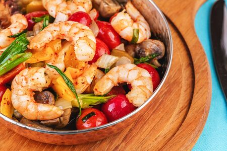 Seafood, Mediterranean cuisine, European dish. Warm salad of grilled fish pieces, shrimps and mussels in a frying pan, with grilled vegetables - with green onions, greens, mushrooms and vegetables.