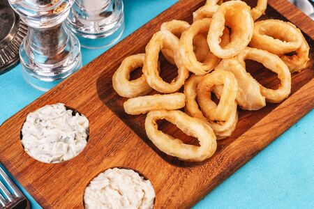 European cuisine, Mediterranean dish. Squid rings fried in batter snack for beer with cream sauce and steamed rice Reklamní fotografie