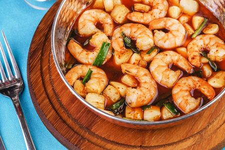 European cuisine, Mediterranean dish. Soup with shrimps, tomatoes, herbs and lemon according to an Italian recipe Фото со стока