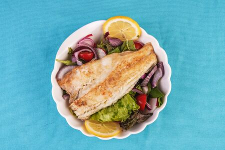 Mediterranean dish, European cuisine. grilled white fish steak on a pillow of lettuce- lemon, arugula, red onion rings, lettuce leaves, cabbage, tomatoes with olive oil