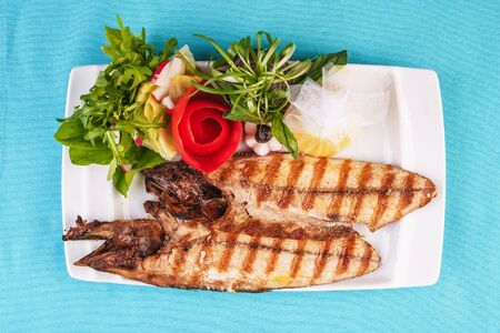 European cuisine, Mediterranean dish. River trout steak, white meat fish, served with vegetables, lemon and arugula and tomato salad