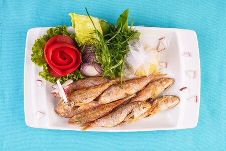 European cuisine, Mediterranean dish. Fried fish in deep fat, capelin in batter with greens, tomatoes, cheese and red onion