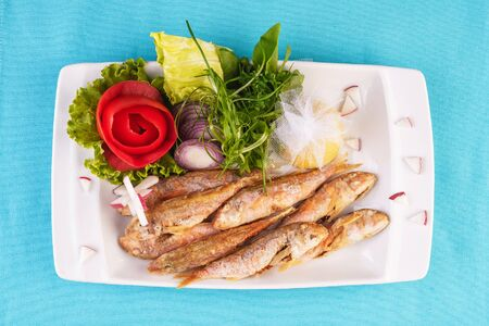 European cuisine, Mediterranean dish. Fried fish in deep fat, capelin in batter with greens, tomatoes, cheese and red onion Stockfoto - 130801132