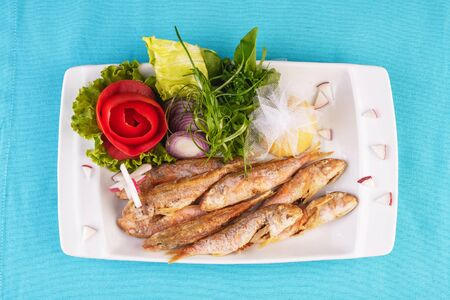 European cuisine, Mediterranean dish. Fried fish in deep fat, capelin in batter with greens, tomatoes, cheese and red onion Stockfoto - 130801131