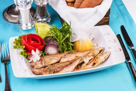 European cuisine, Mediterranean dish. Fried fish in deep fat, capelin in batter with greens, tomatoes, cheese and red onion Stockfoto - 130801141