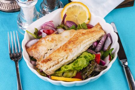 Mediterranean dish, European cuisine. grilled white fish steak on a pillow of lettuce- lemon, arugula, red onion rings, lettuce leaves, cabbage, tomatoes with olive oil Stockfoto