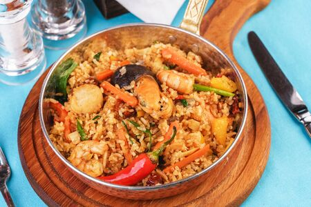 Mediterranean dish, European cuisine. The dish is from Uzbek cuisine. Rice fried with vegetables - greens, carrots, red pepper, onions and seafood - shrimps, mussels and squid. Stockfoto