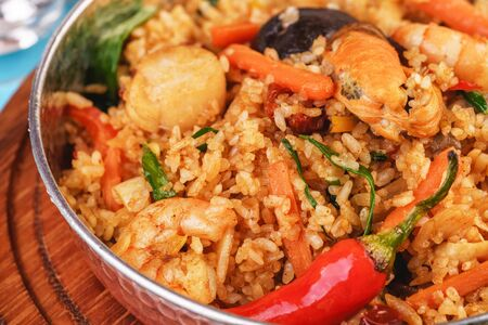 Mediterranean dish, European cuisine. The dish is from Uzbek cuisine. Rice fried with vegetables - greens, carrots, red pepper, onions and seafood - shrimps, mussels and squid. Stockfoto - 130801159