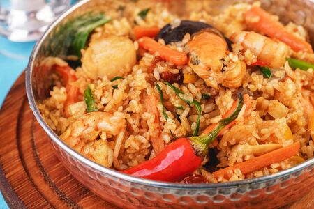 Mediterranean dish, European cuisine. The dish is from Uzbek cuisine. Rice fried with vegetables - greens, carrots, red pepper, onions and seafood - shrimps, mussels and squid. Stockfoto - 130801156