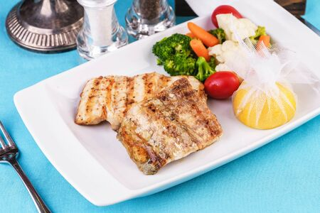 Mediterranean dish, European cuisine. Grilled pieces of fish, served with cooked vegetables - broccoli, cauliflower, cherry tomatoes and lemon Stockfoto - 130801163