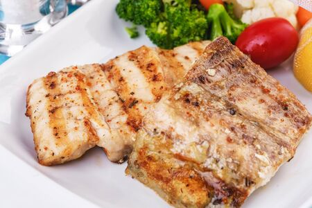 Mediterranean dish, European cuisine. Grilled pieces of fish, served with cooked vegetables - broccoli, cauliflower, cherry tomatoes and lemon