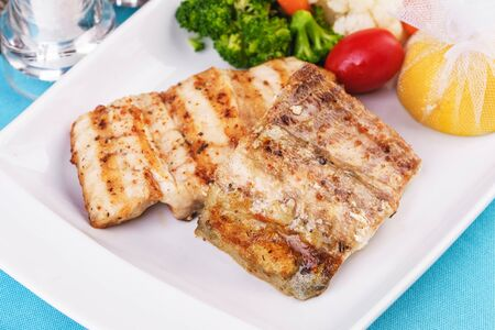 Mediterranean dish, European cuisine. Grilled pieces of fish, served with cooked vegetables - broccoli, cauliflower, cherry tomatoes and lemon Stockfoto - 130801166