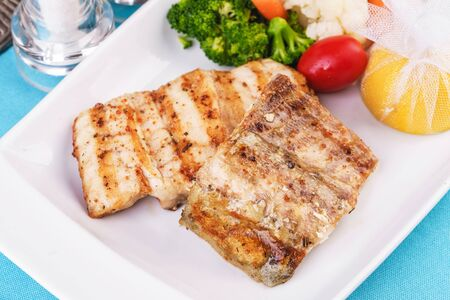 Mediterranean dish, European cuisine. Grilled pieces of fish, served with cooked vegetables - broccoli, cauliflower, cherry tomatoes and lemon Stockfoto - 130801167
