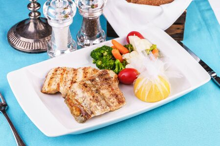 Mediterranean dish, European cuisine. Grilled pieces of fish, served with cooked vegetables - broccoli, cauliflower, cherry tomatoes and lemon Stockfoto - 130801170