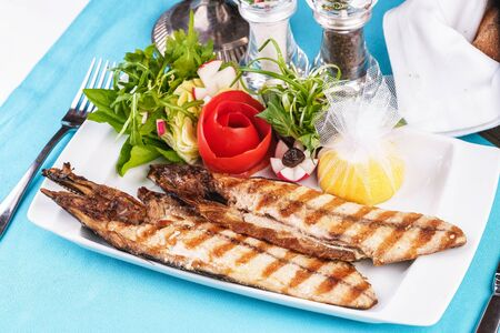 European cuisine, Mediterranean dish. River trout steak, white meat fish, served with vegetables, lemon and arugula and tomato salad Stockfoto - 130801204