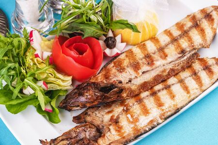 European cuisine, Mediterranean dish. River trout steak, white meat fish, served with vegetables, lemon and arugula and tomato salad Stockfoto - 130801205