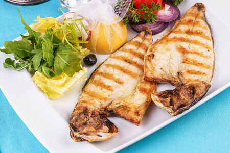 European cuisine, Mediterranean dish. steak of river fish with white meat, served with vegetables, lemon and arugula and tomato salad Stockfoto - 130801207